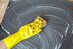 Handen i gul handske tvättar den elektriska ugnpanelen Royaltyfri Bild