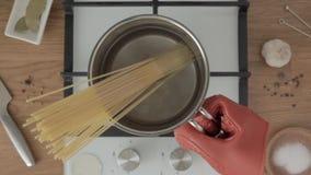 Handen i hals sätter pannan med vatten och spagetti på den arbetande gasugnen