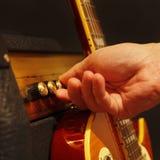 Handen justerar den combo förstärkaren för gitarr med den elektriska gitarren på svart bakgrund Grunt djup av fältet, låg tangent Royaltyfria Bilder