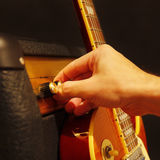 Handen justerar förstärkaren för gitarr med den elektriska gitarren på svart bakgrund Grunt djup av fältet, låg tangent, slut upp Royaltyfri Fotografi