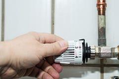Handen justerar termostaten Arkivbilder