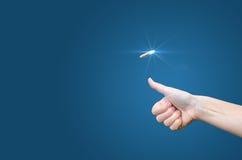 Handen kastar ett mynt på en blå bakgrund för att göra beslutet royaltyfri foto