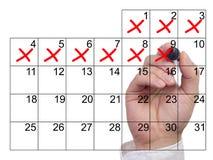 Handen korsar av dagar i rött från en kalender Arkivbild
