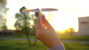 Handen lanserar det pappers- flygplanet mot solnedgångbakgrund långsam rörelse lager videofilmer