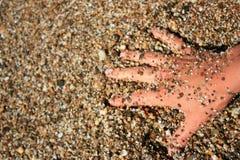 Handen ligger i havskiselstenarna på kusten royaltyfria bilder