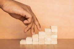 Handen liknar aff?rspersonen som upp kliver en tr?leksaktrappuppg?ng p? tr?texturerad bakgrund arkivbilder