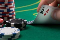 Handen lyfter för två segra kort på en grön pokertabell royaltyfri bild