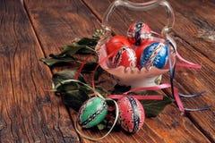 Handen målade easter ägg i en antik exponeringsglasbunke som dekorerades med gröna murgrönafilialer på en tappning, trätabell med arkivbild