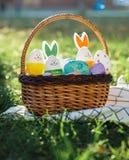 Handen målade påskägg i rottingkorg på grönt gräs med den vita handduken Traditionell garnering för påsk på den soliga vårdagen arkivfoton