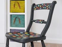 Handen målade stol som målades med Annie Sloan kritamålarfärg, färgglade korgar bakom arkivfoton