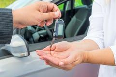 Handen med bilen stämmer och räcker köparen Arkivbild