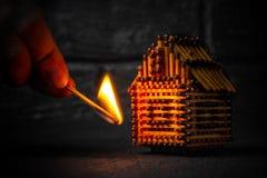Handen med en brinnande match ställer in brand till husmodellen av matcher, risken, skydd för egenskapsförsäkring eller tändning  royaltyfri fotografi