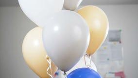 Handen med en kniv tränger igenom ballongerna, och de blåstes bort och exploderar långsam rörelse arkivfilmer