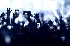 Handen med en smartphone antecknar festival för levande musik royaltyfria bilder