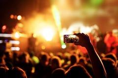 Handen med en smartphone antecknar festivalen för levande musik, den levande konserten, show på etapp royaltyfri bild