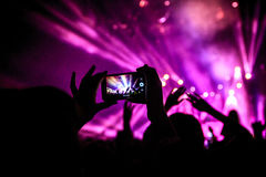 Handen med en smartphone antecknar festivalen för levande musik som tar fotoet av konsertetappen royaltyfri bild