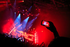 Handen med en smartphone antecknar festivalen för levande musik som tar fotoet av konsertetappen Royaltyfri Fotografi
