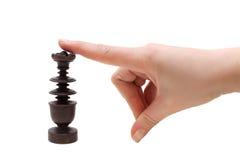 Handen med ett schackstycke på en vit bakgrund Arkivbilder