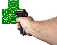 Handen med ett vapen siktade på målet Arkivbild
