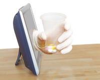 Handen med exponeringsglas med preventivpillerar lutar ut TVskärmen royaltyfria foton