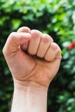 Handen med grep hårt om en näve, mot gröna sidor - näve, makt, ja, gesten royaltyfria foton