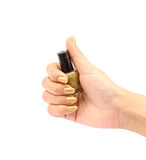 Handen med guld- spikar polermedelflaskan på vit bakgrund Royaltyfri Fotografi