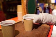 Handen med koppen av funderat vin på jul marknadsför Royaltyfria Foton