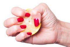Handen med manicured spikar åtstramningcitronen på vit royaltyfri foto