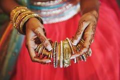 Handen med mehndien av den indiska bruden som rymmer mycket, blänker armbandarmringen med röd legenhabakgrund, närbild arkivbilder