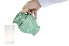 Handen med mjölkar tillbringaren Arkivbild