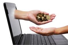 Handen med mynt kommer ut ur bärbar datorbildskärm och häller ner mynt royaltyfri bild