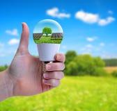 Handen med tummen upp att rymma en eco LEDDE kulan med solpanelen Arkivbilder