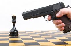 Handen med vapnet tog syfte på schackstycket Fotografering för Bildbyråer