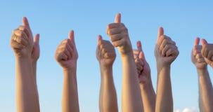 Handen met duimen tegen blauwe hemel omhoog worden opgeheven die stock footage