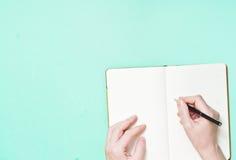 Handen met een lege blocnote met een pen Stock Fotografie