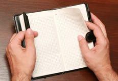 Handen met een notitieboekje Stock Foto's