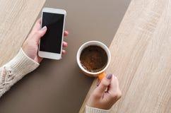 Handen met een telefoon en een kop van koffie Stock Foto