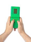 Handen met elektronisch tetrisspel Stock Afbeelding
