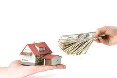 Handen met geld en miniatuurhuis Stock Afbeeldingen