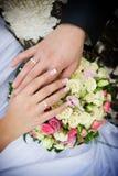 Handen met gouden ringen en boeket Stock Afbeeldingen