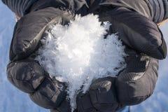 Handen met handschoenen die sneeuw houden stock afbeelding
