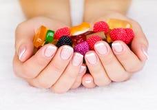 Handen met het suikergoed Stock Afbeelding
