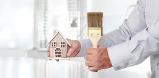 Handen met huis en verfborstel, het concept van de huisdiensten Royalty-vrije Stock Fotografie