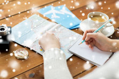 Handen met kaart en koffie die aan notitieboekje schrijven Stock Foto