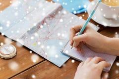 Handen met kaart en kompas die aan notitieboekje schrijven Royalty-vrije Stock Afbeelding