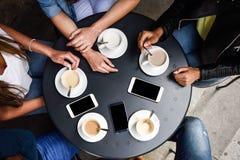 Handen met koffiekoppen en smartphones in een stedelijke koffie Stock Afbeeldingen