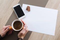 Handen met kop van koffie, chocolade, telefoon en Witboek Royalty-vrije Stock Fotografie