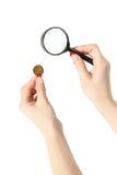 Handen met meer magnifier en muntstuk Royalty-vrije Stock Foto