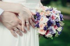Handen met ringen en boeket Stock Foto