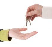 Handen met sleutels die - de sleutels overhandigen Stock Fotografie